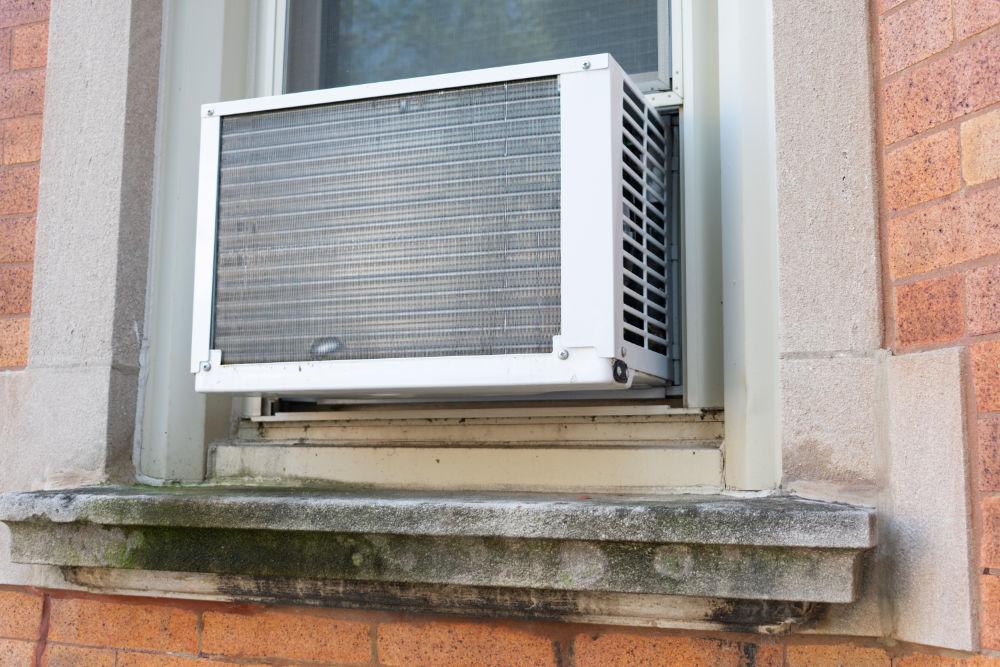 Der überwiegende Teil einer Fenster-Klimaanlage ragt außen hervor.