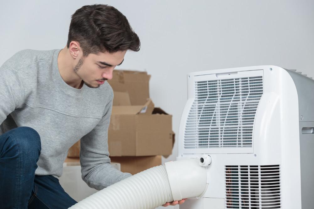 Ein Mann nimmt ein mobiles Klimagerät in Betrieb
