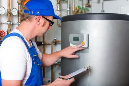 Heizungsmonteur überprüft den Pufferspeicher, um Heizkosten zu sparen.