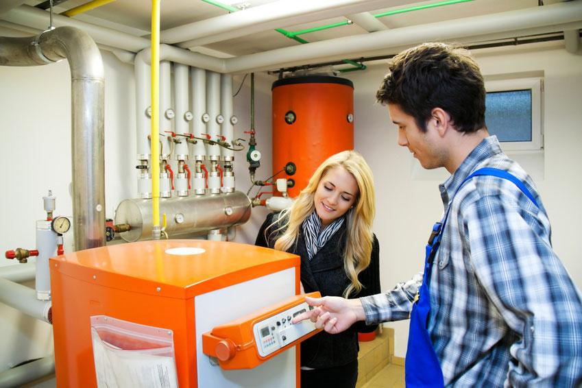 Heizungsmonteur erklärt die Bedienung einer neuen Gasheizung