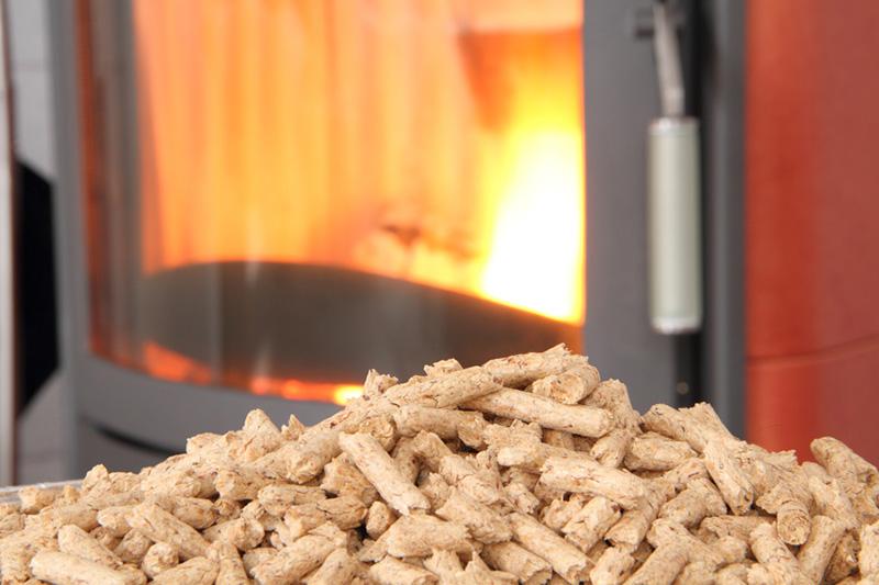 Pelletofen mit Flammenspiel, im Vordergrund Holzpellets