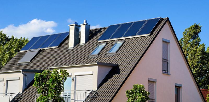 Flachkollektoren einer Solarthermie-Anlage auf einem Hausdach