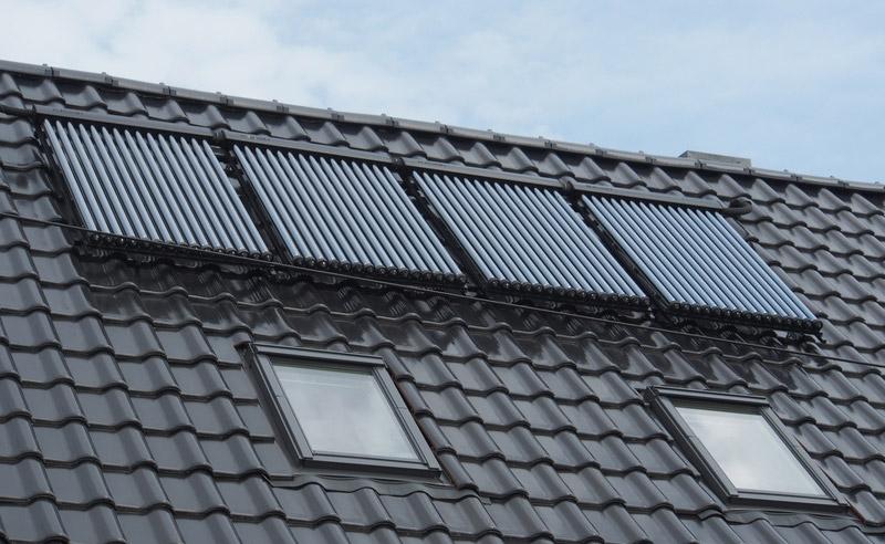 Röhrenkollektoren einer Solarthermie-Anlage auf einem Hausdach